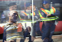 © London News Pictures. 06/09/2015. A man sleeps on a train carrying migrants from Budapest to Vienna at  train station in Hegyeshalom on the border of Hungary and Austria, September 6 2015. Hundreds of migrants have resumed their journey through Austria to Germany after Hungary's decision on Friday to let them through.    Picture by Paul Hackett/LNP