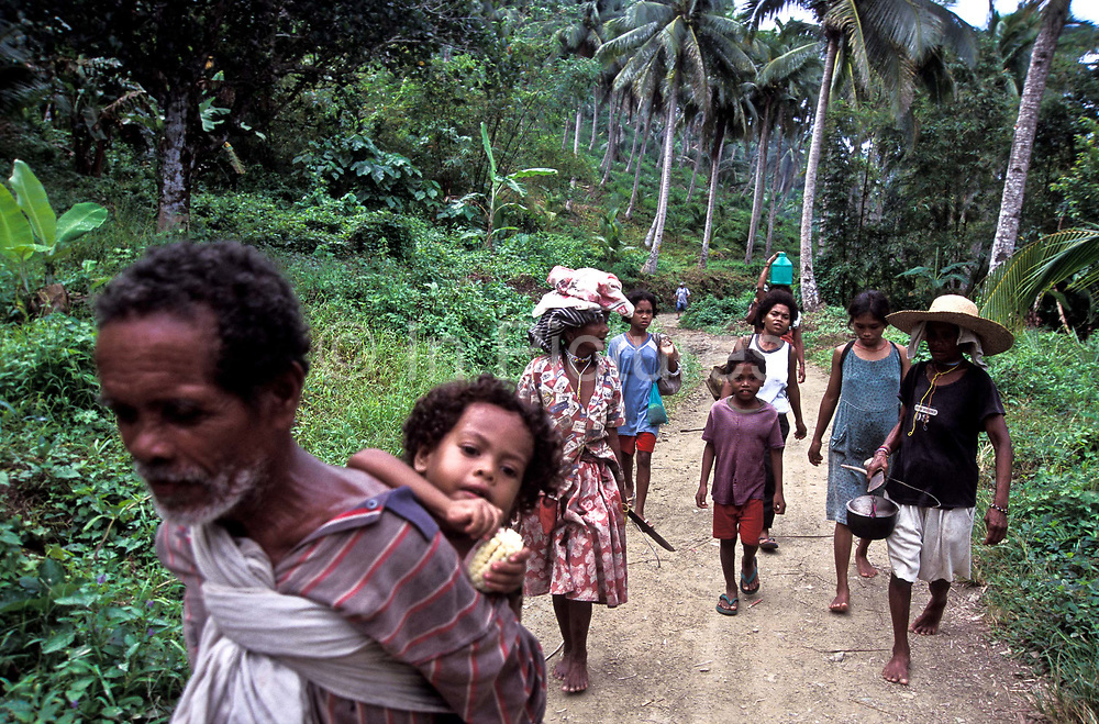 A community of AGTAS (aboriginal natives, similar to pigmies walk through Busok Busok on their way to a day of fishing for crabs, in Gumacas bay, Aurora, Philippines