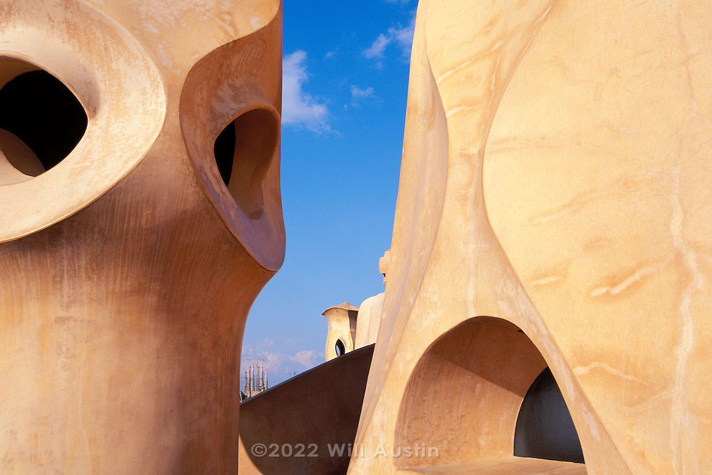 Rooftop of the Casa Mila building designed by Catalan architect Antoni Gaudi in the Eixample District of Barcelona, Spain.  Sometimes known as La Pedrera, it was completed in 1912.  Gaudi's most famous work, the Sagrada Familia, can be seen in the distance.