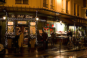 People shelter from rain at night on street corner outside traditional Le Petit Zinc Restaurant, Left Bank, Paris, France