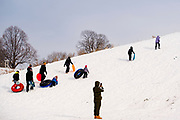 02 JANUARY 2021 - DES MOINES, IOWA: People trudge up the hill below the Iowa Supreme Court during an afternoon of sledding on the hill. The hill is one of the most popular spots in Des Moines for sledding and winter play. Hundreds of people took advantage the warmer weather and the week's record snow to spend time on the slopes around the Supreme Court and neighboring capitol. The high temperature Saturday was about 25F (-4C).     PHOTO BY JACK KURTZ