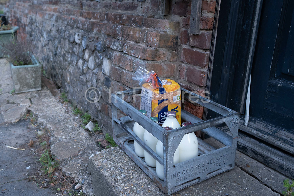 Early morning milk and bread delivery left in a crate on the doorstep of a property known as Geoffrey the Dyers house, in Worstead, a village whose wealth came from the 14th century weaving industry, on 10th August 2020, in Worstead, Norfolk, England.
