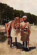 Indian cavalryman in campaign kit, standing beside his mount, c1914.