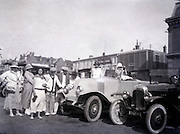group posing with car about 1920s
