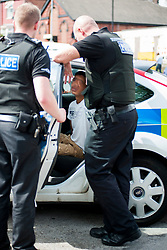 South Yorkshire Police NE Sheffield Safer Neighburhoods Team working in the Page Hall area of Sheffield Police officer arrest a 15 year old after a stop and search<br /> <br /> 15 August 2013<br /> Image © Paul David Drabble<br /> www.pauldaviddrabble.co.uk