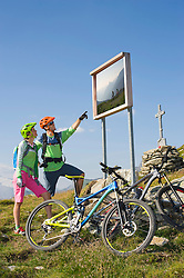 Young couple of mountain bikers watching information board on uphill, Zillertal, Tyrol, Austria