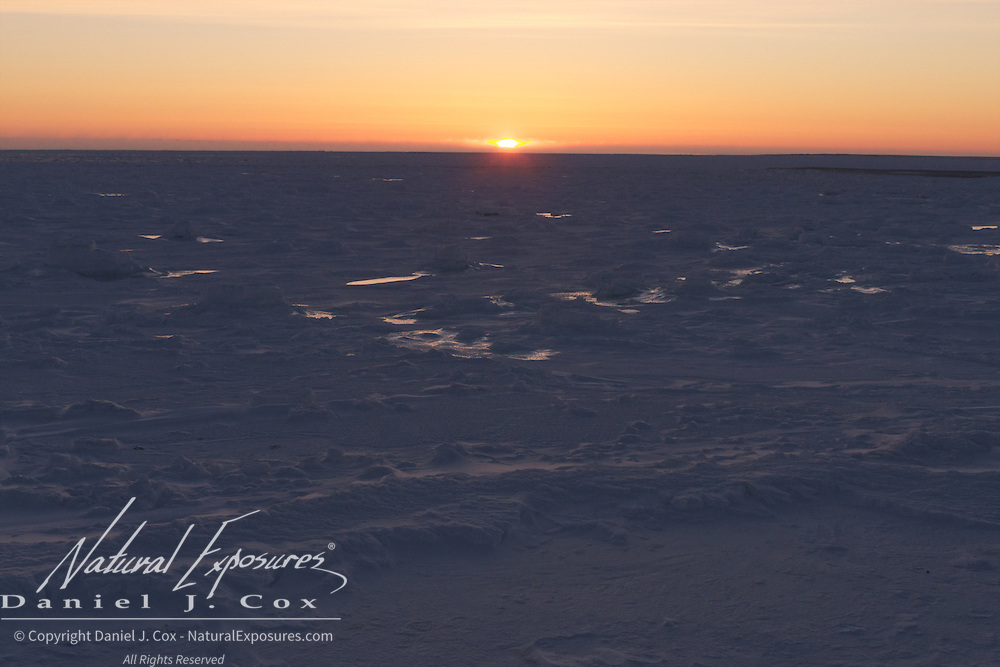The sun sets over the frozen ice on Hudson Bay, Cape Churchill, Manitoba.