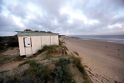 30 June 2020. South of Calais, France.<br /> Smugglers' paradise. A deserted beach south of Calais where local police claim migrants often attempt the treacherous crossing to Great Britain. Items found in a shack and caravan including passport photos, empty water bottles, mattresses and cardboard used as bedding clearly indicate the seemingly derelict premises hidden in the sand dunes have recently been used. The location is reasonably remote and backs onto farmland. A gravel access road makes this a prime location for ruthless criminal gangs to drop migrants paying as much as €5,000 for a ticket on an inflatable dinghy with a small outboard motor and less for surfboards and inflatable kayaks. Local police claim it is from here and other remote beaches in the region that migrants often set out to make desperate and dangerous attempts to cross one of the busiest shipping lanes in the world. Migrants are crossing the English Channel (La Manche) by boat, kayak, surf board and even inflatable paddling pools as numbers seeking asylum in the UK continue to rise. <br /> Photo©; Charlie Varley/varleypix.com