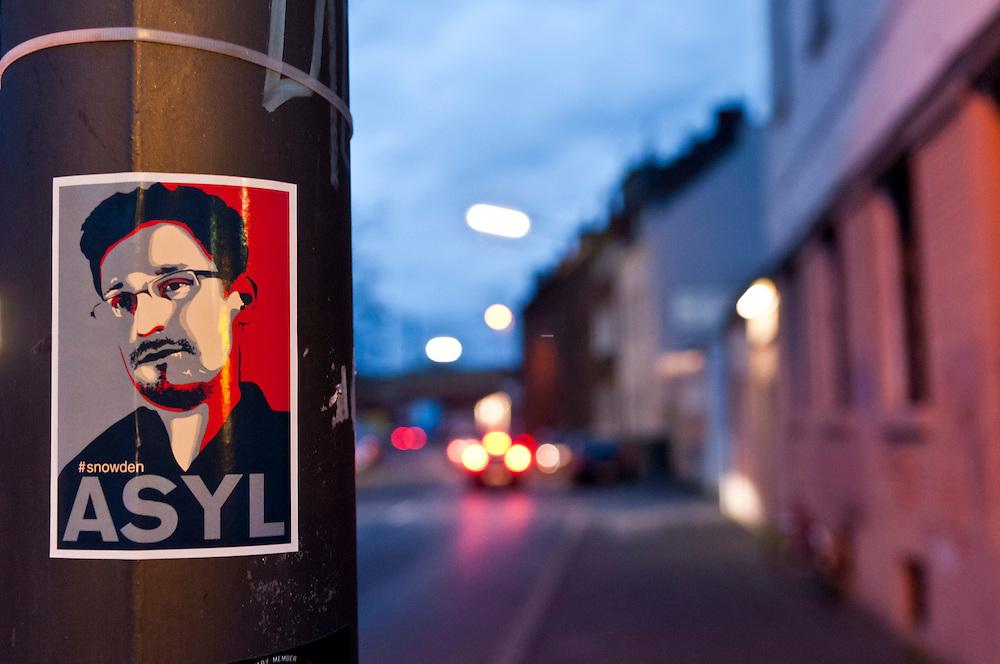 """Deutschland, Nordrhein-Westfalen,Köln,Ehrenfeld,Heilig Abend, Auf einem Laternenpfahl in Köln Ehrenfeld klebt ein Poster das den amerikanischen Whistleblower Edward Joseph Snowden im grafischen Stil des Plakates des US-amerikanischen Präsidenten Barack Obamas  für die Kampagne """"Hope"""" entworfen von dem Künstler Shepard Fairey, mit der Aufschrift ASYL und dem Hashtag - Doppelkreuz #snowden was auf die entsprechende Twitter-Seite verweist, zeigt. Seine Enthüllungen gaben Einblicke in das Ausmaß der weltweiten Überwachungs- und Spionagepraktiken von US-Diensten und lösten so die Überwachungs- und Spionageaffäre 2013 aus.     Germany, Cologne, Koeln, A poster at a pole on Christmas Eve showing the image of Edward Joseph Snowden. The poster is an imitation of Barack Obama´s HOPE poster designed by  Shepard Fairey, which was widely described as iconic and came to represent the 2008 Obama presidential campaign. Instead of HOPE there is the word ASYL asylum and a hashtag #snowden for a twitter page       """