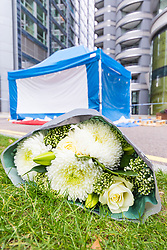 A local resident leaves a floral tribute at The Corniche as a police cordon surrounding a forensics tent remains in place outside on the Albert Embankment in London after a window pane fell yesterday morning killing passing coach driver Mick Ferris. Albert Embankment, London, October 03 2018.