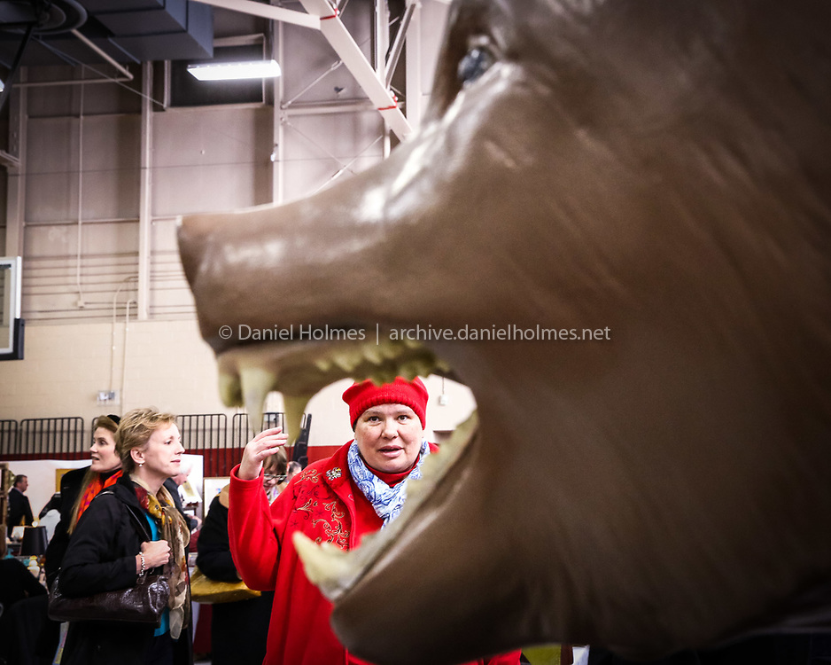 (2/22/14, HOLLISTON, MA) Ruth Montgomery of Sudbury his framed in the jaws of a massive resin grizzly bear during the 47th Holliston Antique Show at Holliston High School on Saturday. The event was sponsored by the Holliston Scholarship Foundation with proceeds going to local scholarships. Daily News and Wicked Local Photo/Dan Holmes