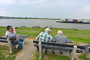 Nederland, Beneden Leeuwen, Waal, 7-5-2013Druk verkeer van binnenvaartschepen op de waal, rijn, vooral op en neer het duitse ruhrgebied en de haven van rotterdam. Enkele oudere mannen kijken vanaf de dijk en op een bankje naar het scheepvaartverkeer.Foto: Flip Franssen/Hollandse Hoogte