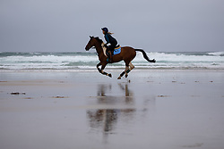 © Licensed to London News Pictures. 04/07/2020. Perranporth, UK. Tina Wallace rides a horse along Perranporth beach in Cornwall today, despite wet weather. Today marks a lift in COVID-19 restrictions, as pubs are allowed to open, whilst customers must still follow social distancing guidelines. Tens of thousands of tourists are due to arrive in Cornwall over this weekend, as overnight stays within England are also allowed. Photo credit : Tom Nicholson/LNP