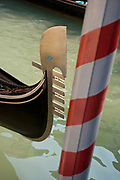 Close up of ornate bow of a gondola and striped protective pole, Venice, Italy