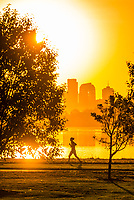 People jogging at sunrise at Sloans Lake with Downtown Denver in background, Colorado USA. Sloan's Lake is the biggest lake in Denver, and at 177 acres, it's the city's second largest park.