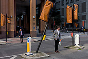 A leaning traffic light pole and covered others in a City of London street.