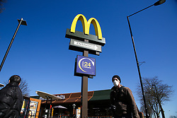© Licensed to London News Pictures. 23/03/2020. London, UK. A man wearing a face mask walks past McDonald's in Haringey north London. McDonald's restaurants across the UK are to close from 7pm tonight as the spread of the coronavirus continues in the country. Photo credit: Dinendra Haria/LNP