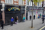 "The UK Chancellor Rishi Sunak has said it is ""very likely"" the UK is in a ""significant recession"" due to the Coronavirus pandemic lockdown, as figures show the economy contracting at the fastest pace since the financial crisis. And in the face of continued lockdown on the high street such as here on the Walworth Road in south London, a queue of shippers observe social distancing in front of shuttered businesses, on 13th May 2020, in London, England."
