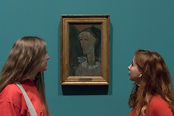 "© Licensed to London News Pictures. 21/11/2017. London, UK.  Staff members view ""Self Portrait as Pierrot"", 1915.  Preview of ""Modigliani"", the most comprehensive exhibition of works by Amedeo Modigliani ever held in the UK.  On display are iconic portraits, sculptures and 12 nudes, the largest group ever shown in the UK.  The show runs 23 November to 2 April 2018.  Photo credit: Stephen Chung/LNP"