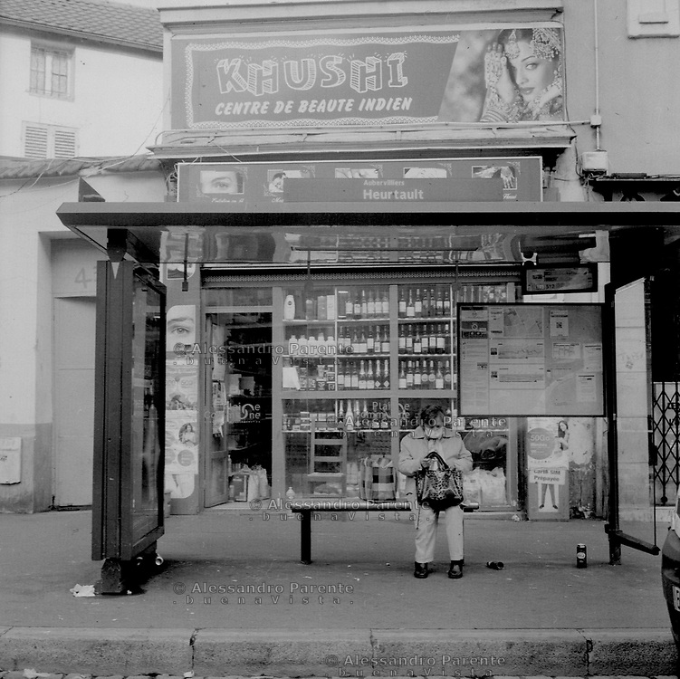 Aubervilliers, Seine Saint Denis. An old woman is waiting for the bus in front of an open indian beauty center.