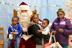 Families had the change to pose for pictures with Santa during the Winter Fest celebration at the community room the Free Library branch in Olney, on December 15, 2018. (Bastiaan Slabbers for WHYY)