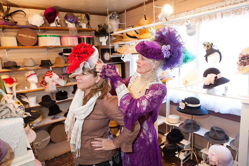 A guest trying on hats in the gift shop with Alyce Cornyn-Selby, the Founder and Executive Director of The Hat Museum in Portland, Oregon