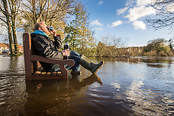 © Licensed to London News Pictures. 19/11/2015. Boroughbridge UK. A man sits on a half submerged park bench drinking tea in a flooded park in the Centre of Boroughbridge in Yorkshire. The Environment Agency have issued 12 flood alerts for the county & more flooding is expected.Photo credit: Andrew McCaren/LNP