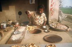Man making nan bread in Tandoori oven,