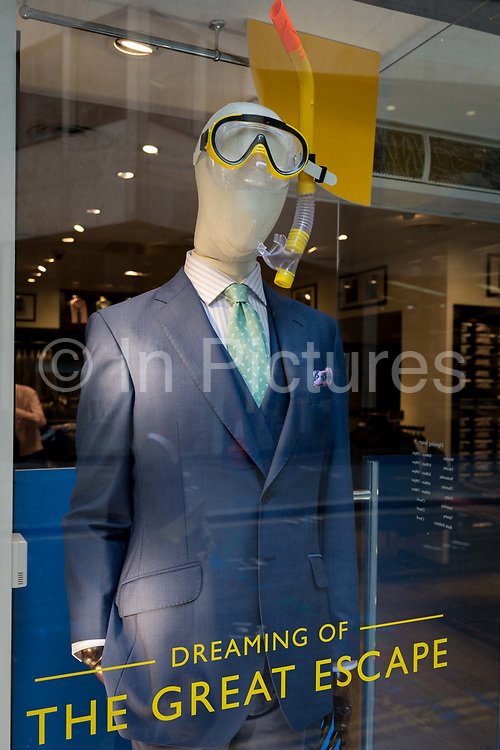 A menswear shop window featuring the idea of summer holidays and escapism, on 4th June 2018, in London, England.