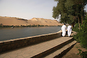 Men walking on promenade along Nile River on Kitchener's Island, Aswan, Egypt