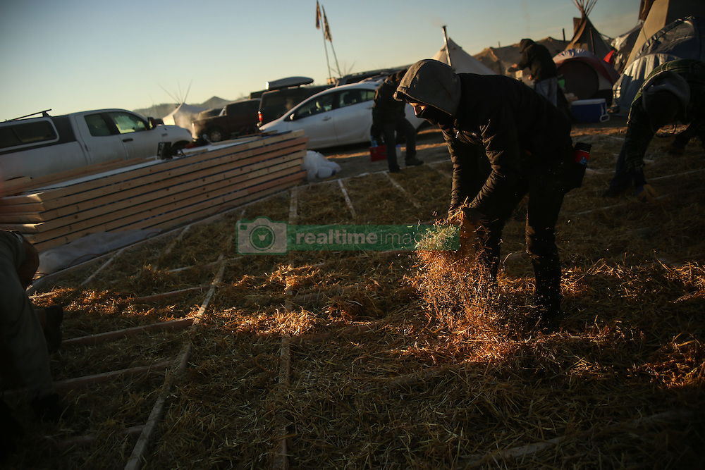 November 25, 2016 - Cannon Ball, North Dakota, U.S - JOSH TYBRING of Wisconsin places hay at the foundation of a permanent winter structure being built at the Oceti Sakowin Camp at the Standing Rock Indian Reservation in Cannon Ball, North Dakota. (Credit Image: © Joel Angel Ju‡Rez via ZUMA Wire)