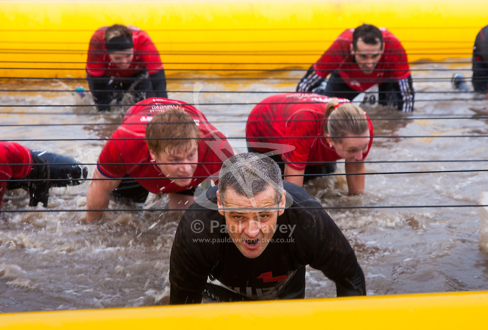 Wembley, London November 22nd 2014. Thousands of competitors in teams compete in the Men's Health Survival of the Fittest event, raising money for various charities. Event organisers Rat Race created the challenging course, with various obstacles from mud pools to scaffolding climbing frames, with both serious and not-so-serious athletes competing for glory. PICTURED: Eyes focused on completing the course, a competitor crawls through the freezing, muddy water.