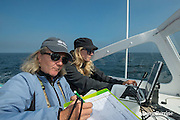 senior scientist Dr. Moira Brown instructs research intern Johanna Anderson in using the onboard data logging software program aboard the New England Aquarium research vessel Nereid while searching the Bay of Fundy for North Atlantic right whales