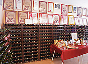 Plenty of bottles stacked on shelves and many diplomas from wine competitions framed on the wall., in the winery tasting room. Vukoje winery, Trebinje. Republika Srpska. Bosnia Herzegovina, Europe.