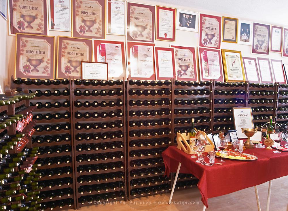 Plenty of bottles stacked on shelves and many diplomas from wine competitions framed on the wall., in the winery tasting room. Vukoje winery, Trebinje. Republika Srpska. Bosnia Herzegovina, Europe.