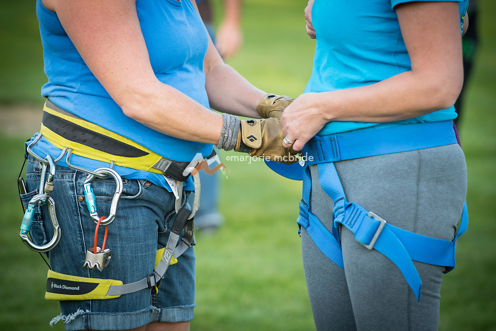 Instructor doing up straps on harness at College of Southern Idaho Challenge Rope Course Twin Falls, Idaho.