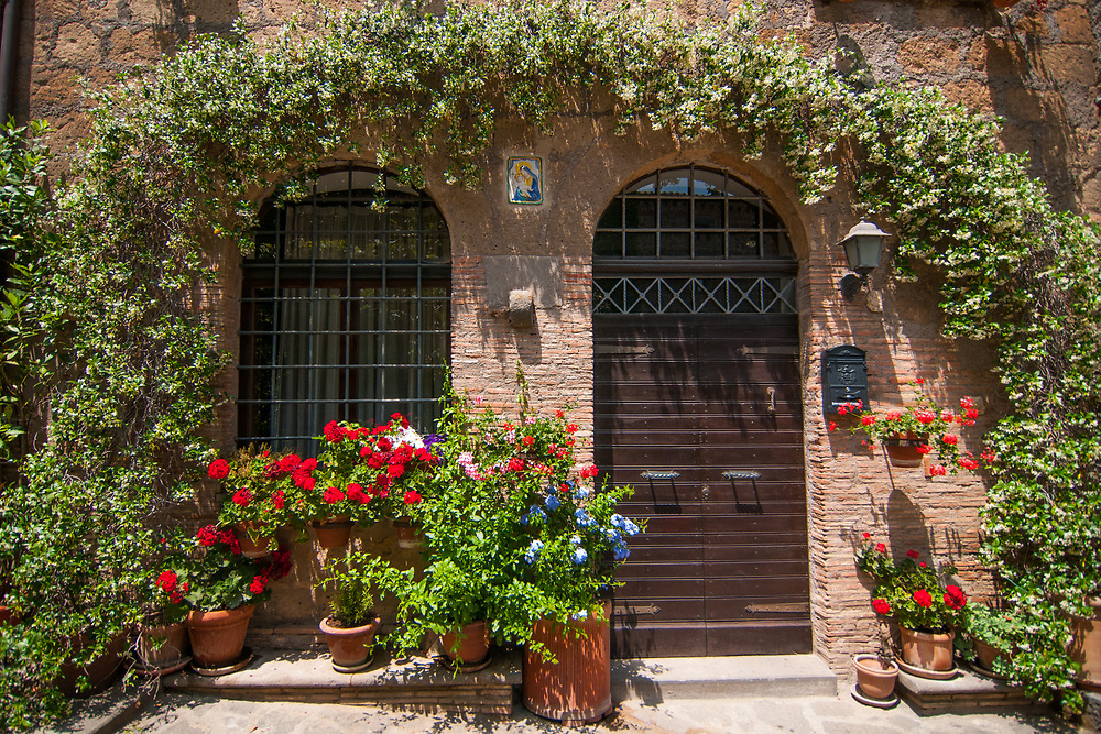 """Doors and flowers of a house of the village of Civita di Bagnoregio.<br /> Civita di Bagnoregio is a town in the Province of Viterbo in central Italy, a suburb of the comune of Bagnoregio, 1 kilometre (0.6 mi) east from it. It is about 120 kilometres (75 mi) north of Rome. Civita was founded by Etruscans more than 2,500 years ago. Bagnoregio continues as a small but prosperous town, while Civita became known in Italian as La città che muore (""""The Dying Town""""). Civita has only recently been experiencing a tourist revival. The population today varies from about 7 people in winter to more than 100 in summer.The town was placed on the World Monuments Fund's 2006 Watch List of the 100 Most Endangered Sites, because of threats it faces from erosion and unregulated tourism."""