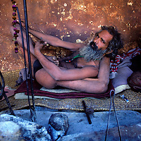 NEPAL, Kathmandu. An ascetic yogi practices one of his many positions in pilgrim's shelter at  Pashupatinath Temple.