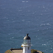 Cape Reinga Lighthouse at the north western most tip of the Aupouri Peninsula, at the northern end of the North Island of New Zealand. . Cape Reinga is  a favourite tourist attraction and the meeting point  between the Tasman Sea to the west and the Pacific Ocean to the east. From the lighthouse it is possible to watch the tidal race, as the two seas clash to create unsettled waters just off the coast. Cape Reinga, North Island, New Zealand, 21st November 2010. Photo Tim Clayton.