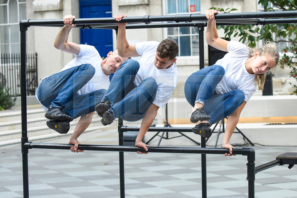 """© Licensed to London News Pictures. 10/10/2019. LONDON, UK.  (L to R) Alister O'Loughlin, Tim Merrifield and Grace Sellwood, members of the Urban Playground Parkour Team, rehearse """"Zoo Humans"""" in the courtyard of Guy's Hospital adjacent to The Shard building to kick of the Dance Umbrella 2019 festival.  The show is inspired by the shocking statistic that three quarters of young people in the UK spend less time outdoors than prisoners  Photo credit: Stephen Chung/LNP"""