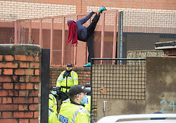 © Licensed to London News Pictures; 10/03/2021; Bristol, UK. A squatter does a yoga pose against the fence of Bristol Prison as Police and bailiffs try to evict a squatted building on Gloucester Road in North Bristol. The squatters say they are called The Pigeon Shit Collective, because of the Government's failings, and they are giving support to homeless people and those in need during the covid-19 coronavirus pandemic. Photo credit: Simon Chapman/LNP.