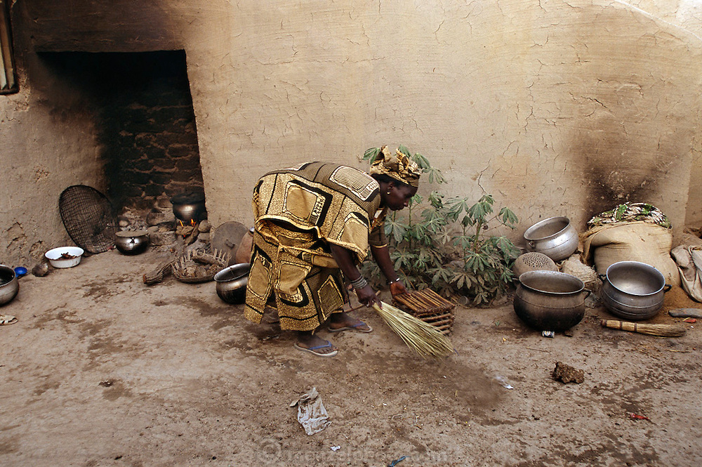 (MODEL RELEASED IMAGE). Pama sweeps the courtyard where she and her co-wife Fatoumata cook the meals for their large family. (From a photographic gallery of kitchen images in Hungry Planet: What the World Eats, p. 55). The Natomo family of Kouakourou, Mali, is one of the thirty families featured, with a weeks' worth of food, in the book Hungry Planet: What the World Eats.