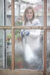 Cleaning greenhouse windows with a pressure washer.
