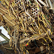 In the heat and dust of the arid Sonoran desert are the remains of a Boeing 747 cockpit at the storage facility at Mojave, California. The wiring of the now-extinct flight engineer's console is a jumble of old technology. Either by age or cooling economy airliners are either cannibalised for still-working parts or recycled for scrap, their aluminium fuselages worth more than their sum total. Elsewhere, assorted aircraft wrecks sit abandoned in the scrub minus their bellies, legs or wings like dying birds. After a lifetime of safe commercial flight, wings are clipped and cockpits sliced apart by huge guillotines, cutting through their once-magnificent engineering. Picture from the 'Plane Pictures' project, a celebration of aviation aesthetics and flying culture, 100 years after the Wright brothers first 12 seconds/120 feet powered flight at Kitty Hawk,1903.