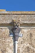 Gargoyle grotesque face drainpipe on wall medieval church of Saint John, Inglesham, Wiltshire, England, UK