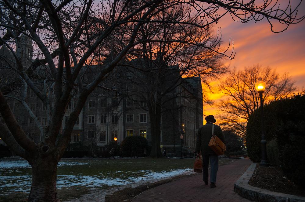 A briefcase carrying man walks through Georgetown University at sunset. Washington, D.C.