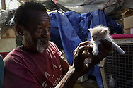 """Q aka """"Father Mom"""", from Milwaukee, Wisconsin, has been in Slab City since 2007. He runs a cat sanctuary with his 30 year partner Doc.  They have 68 cats currently, with some of the cleanest cages and litter boxes ever seen. They created a non-profit called Paw Town Cats they operate from their bus residence which is remarkable considering they have no public resources on squatted land."""