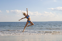 Young woman in a bikini jumping gracefully on the beach