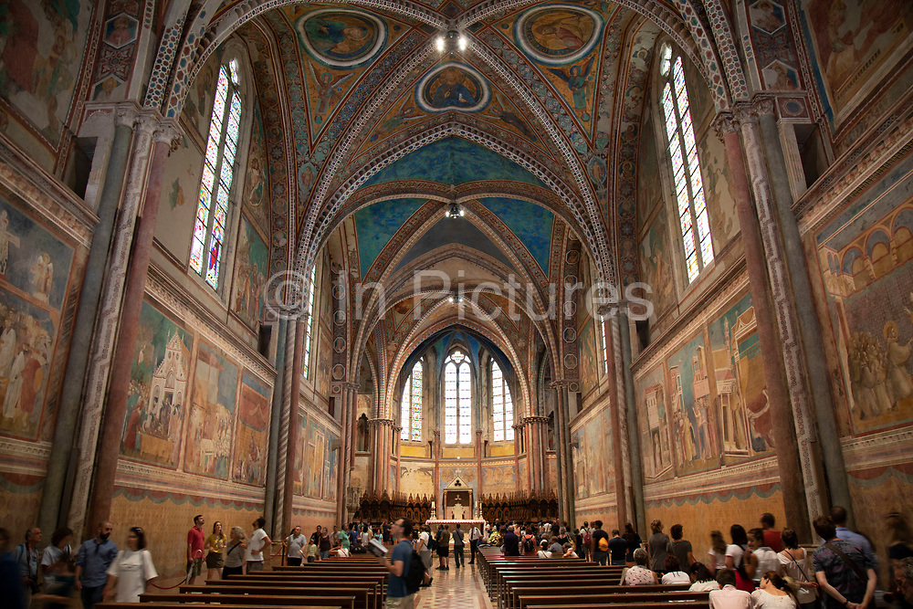 Ornately painted interior of the Basilica of San Francesco dAssisi in Assisi, Umbria, Italy. The Papal Basilica of Saint Francis of Assisi is the mother church of the Roman Catholic Order of Friars Minor Conventual in Assisi, a town of Umbria region in central Italy, where Saint Francis was born and died. The basilica is one of the most important places of Christian pilgrimage in Italy. Assisi is a town in the Province of Perugia in the Umbria region, on the western flank of Monte Subasio. It is generally regarded as the birthplace of the Latin poet Propertius, and is the birthplace of St. Francis, who founded the Franciscan religious order in the town in 1208, and St. Clare, Chiara dOffreducci, the founder of the Poor Sisters, which later became the Order of Poor Clares after her death. Assisi is now a major tourist destination for those sightseeing or for more religious reasons.
