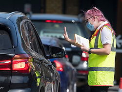 © Licensed to London News Pictures. 20/05/2020. Staines, UK. A McDonalds employee hands out leaflets to customers as they queue at a McDonalds Drive Thru in Staines, Surrey. Branches of McDonalds restaurants have opened for drive thru today for the fist time since lockdown.  todayGovernment has announced a series of measures to slowly ease lockdown, which was introduced to fight the spread of the COVID-19 strain of coronavirus. Photo credit: Ben Cawthra/LNP